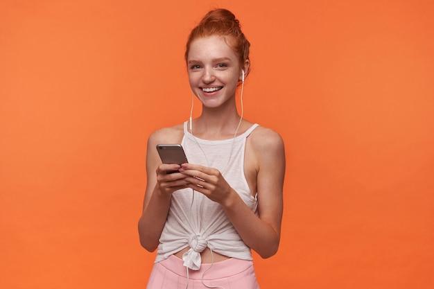 Studio foto van charmante jonge readhead vrouw met broodje kapsel poseren op oranje achtergrond, smartphone in opgeheven handen houden en luisteren naar muziek met koptelefoon