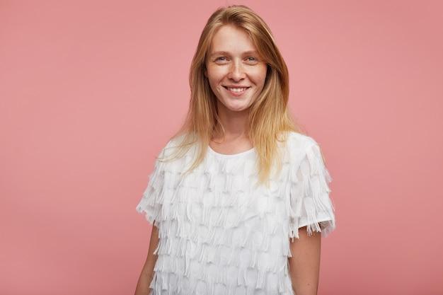 Studio foto van charmante roodharige jongedame met natuurlijke make-up kijken positief camera met aangename glimlach, poseren op roze achtergrond met handen naar beneden