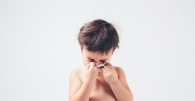 Studio foto van een baby met zakdoek. het zieke geïsoleerde kind heeft loopneus.