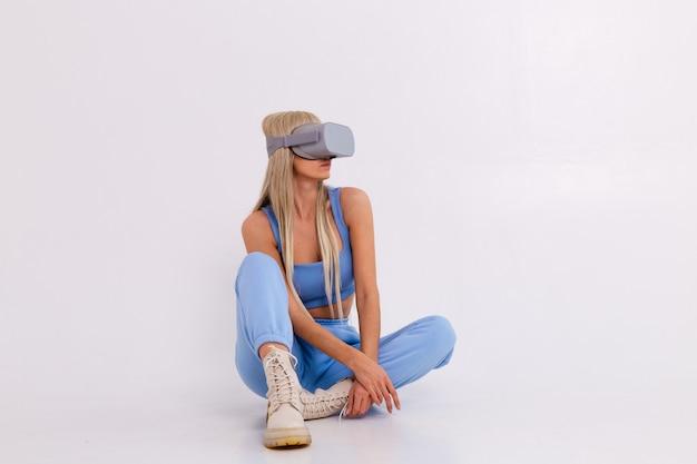 Studio foto van een jonge aantrekkelijke vrouw in een warm blauw modieus pak virtual reality bril
