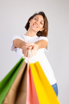 Studio foto van europese vrouw met boodschappentassen op witte achtergrond