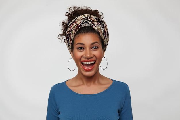 Studio foto van gelukkige jonge donkerharige trendy krullend dame vrolijk lachen terwijl ze zich verheugt over iets, geïsoleerd op witte achtergrond met handen naar beneden