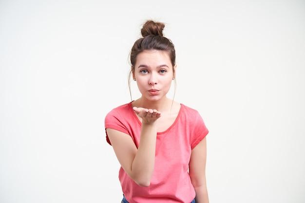 Studio foto van jonge aantrekkelijke bruinharige dame die de handpalm omhoog houdt terwijl ze een luchtkus blaast naar de camera, staande op een witte achtergrond in een roze t-shirt