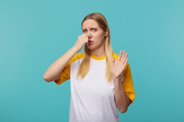 Studio foto van jonge blauwogige blonde dame met fronsende wenkbrauwen en het sluiten van haar neus terwijl ze slechte geuren vermijdt, geïsoleerd op blauwe achtergrond in casual t-shirt