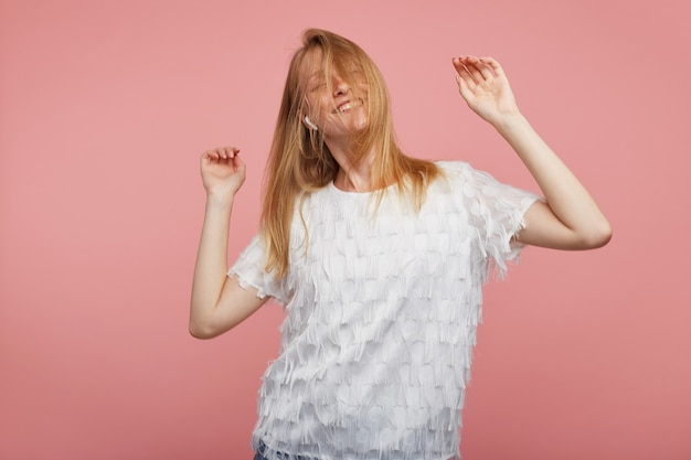 Studio foto van jonge blij roodharige vrouw zwaaien met haar foxy haar tijdens het dansen met opgeheven handen, vrolijk glimlachend terwijl poseren op roze achtergrond