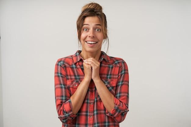 Studio foto van jonge bruinharige dame met broodje kapsel verrast haar groene ogen afronden terwijl ze naar de camera kijkt en de handen gevouwen houdt, geïsoleerd op witte achtergrond