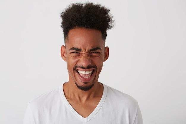 Studio foto van jonge brunette bebaarde man met kort trendy kapsel met zijn witte perfecte tanden