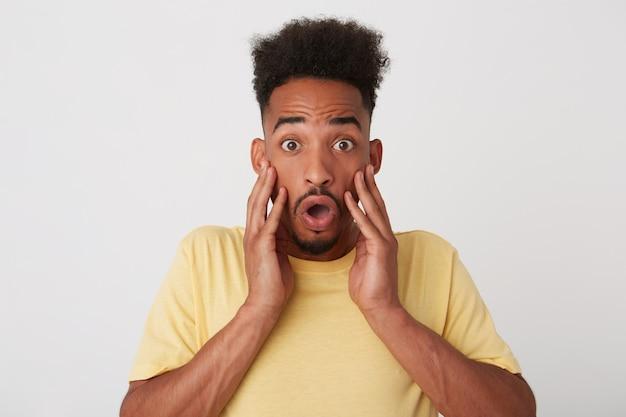 Studio foto van jonge geschokt brunette kortharige man met donkere huid met palmen op zijn gezicht