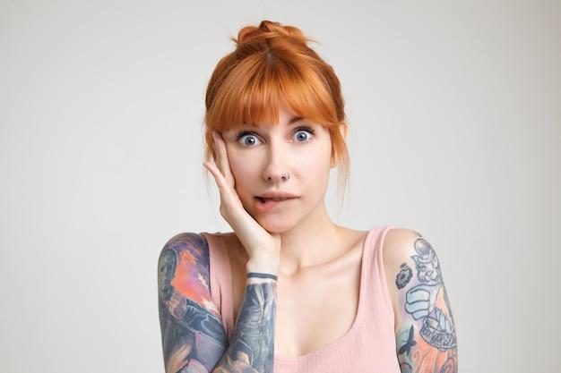 Studio foto van jonge groenogige roodharige getatoeëerde vrouw die onderlip bijt terwijl ze verward naar de camera kijkt, met opgeheven hand op haar gezicht terwijl ze poseren op witte achtergrond