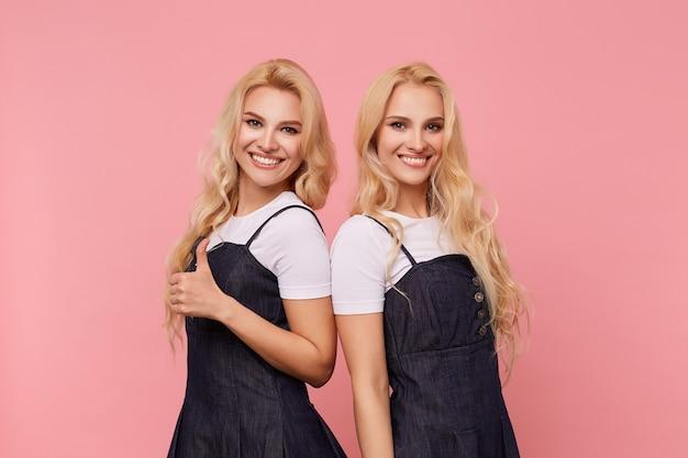 Studio foto van jonge langharige witharige dames tonen hun witte perfecte tanden terwijl ze gelukkig naar de camera kijken met een brede glimlach, geïsoleerd op roze achtergrond