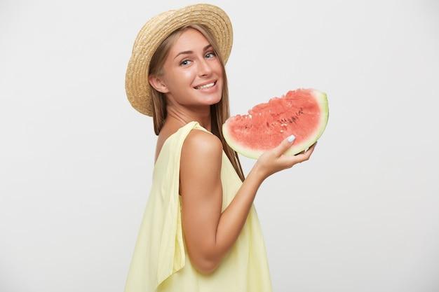 Studio foto van jonge mooie blonde vrouw met natuurlijke make-up dragen boater hoed terwijl poseren op witte achtergrond met watermeloen, vrolijk glimlachend naar camera