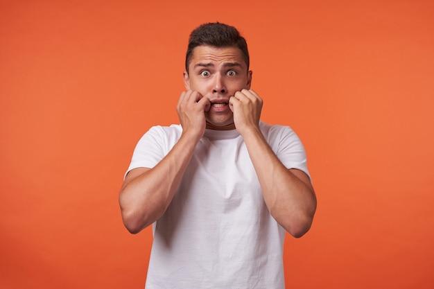 Studio foto van jonge mooie bruinharige man met opgeheven handen op zijn wangen terwijl hij bang naar de camera kijkt, staande tegen een oranje achtergrond