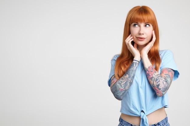 Studio foto van jonge mooie getatoeëerde vrouw met lang foxy haar met opgeheven handen op haar wangen terwijl ze verwonderd opzij kijkt, geïsoleerd op witte achtergrond