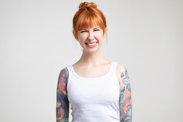 Studio foto van jonge mooie roodharige vrouw met tatoeages met haar ogen dichtgeknepen terwijl ze vreugdevol lacht, in hoge geest zijn terwijl poseren op witte achtergrond