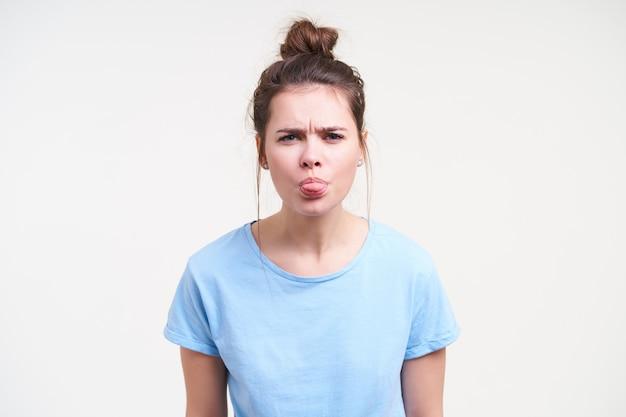 Studio foto van jonge sombere donkerharige vrouw met knot kapsel haar wenkbrauwen fronsen en tong tonen terwijl staande op witte achtergrond met handen naar beneden
