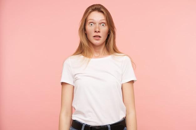 Studio foto van jonge verbaasd langharige roodharige dame die verrast haar groene ogen rondt terwijl ze naar de camera kijkt, geïsoleerd op roze achtergrond in wit basic t-shirt