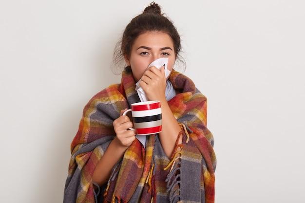 Studio foto van jonge vrouw met zakdoek en beker in handen.