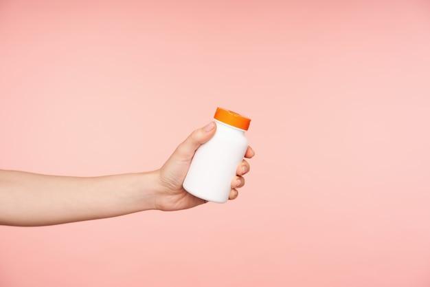 Studio foto van jonge vrouwelijke hand met naakt manicure fles met pillen erin houden terwijl wordt geïsoleerd op roze achtergrond. gezondheidszorg en schoonheidsconcept