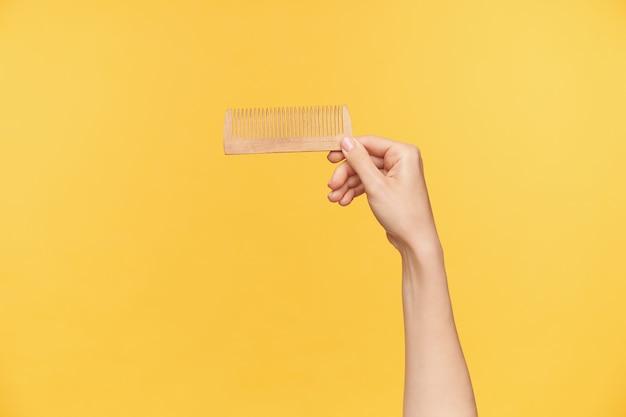 Studio foto van jonge vrouwelijke hand met naakt manicure haarborstel horizontaal houden terwijl poseren op oranje achtergrond. haarverzorging en mensenhanden concept