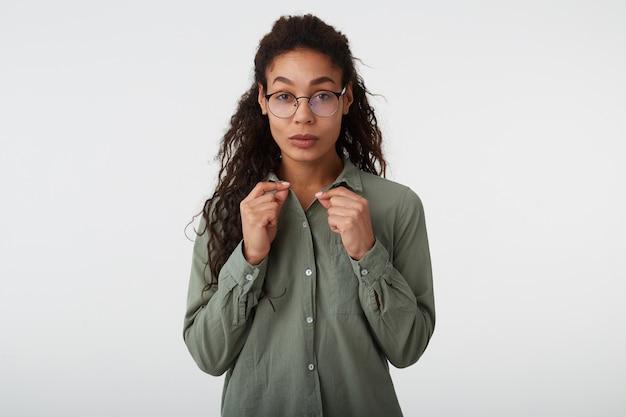 Studio foto van jonge zelfverzekerde krullend brunette donkere huid vrouw met casual kapsel houden opgeheven handen op haar shirt terwijl poseren op witte achtergrond