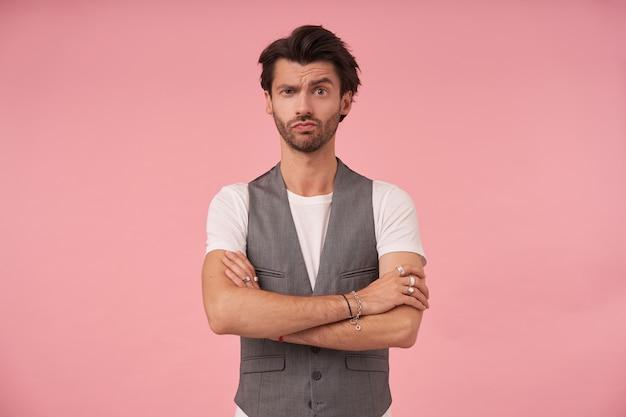 Studio foto van knappe donkerharige man permanent over roze achtergrond in grijs gilet en wit t-shirt, camera kijken met opgetrokken wenkbrauw, armen gekruist op de borst en lippen tuit