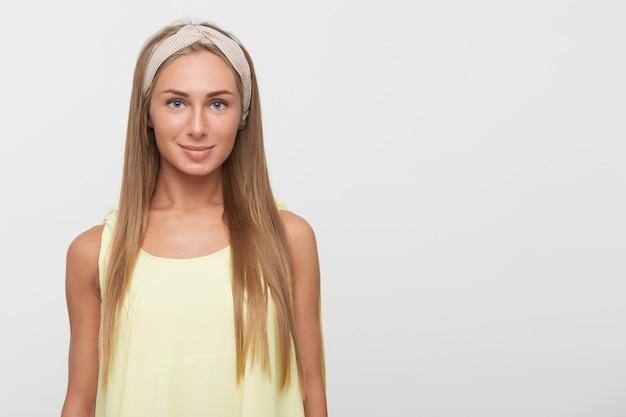 Studio foto van mooie jonge blauwogige blonde vrouw draagt beige hoofdband terwijl staande op witte achtergrond positief naar camera kijken met lichte glimlach