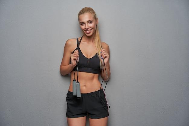 Studio foto van mooie jonge sportieve blonde vrouw op zoek positief naar camera met charmante glimlach, gekleed in zwarte top en korte broek, staande over de lichtgrijze achtergrond met springtouw op haar nek