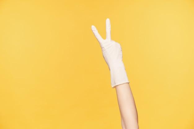 Studio foto van opgeheven hand met twee vingers tijdens het demonstreren van vredesgebaar, poseren op oranje achtergrond. menselijke handen en gebaren concept