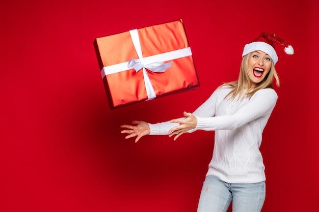 Studio foto van opgewonden blonde dame in kerstmuts gooien geschenkdoos in de lucht met haar mond wijd open. kopieer ruimte
