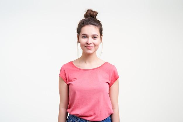 Studio foto van positieve jonge mooie bruinharige vrouw met natuurlijke make-up glimlachend zachtjes naar de camera terwijl staande op een witte achtergrond met handen naar beneden