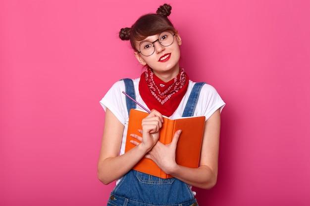 Studio foto van schattige vrouwelijke tiener met twee grappige trossen, met agenda en pensil in handen, direct op zoek
