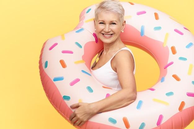 Studio foto van stijlvolle vrolijke vrouw van middelbare leeftijd in witte tabk top met opblaasbare zwemcirkel, chillen op het strand, genieten van warme zonnige dag, camera kijken met een blije, vrolijke glimlach