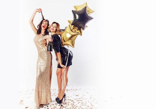 Studio foto van twee geweldige sexy vieren vrouw met rode lippen, lachen, poseren op witte achtergrond. een fles champagne vasthouden, plezier maken. volledige lengte.