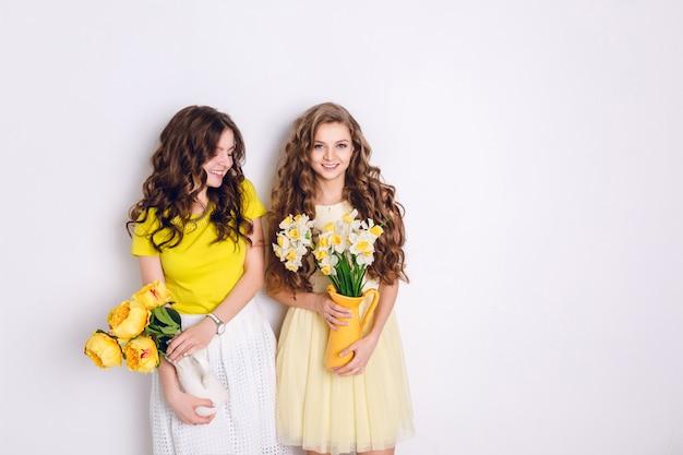 Studio foto van twee staande lachende meisjes. een blond meisje en een donkerbruin meisje houden vazen met bloemen vast.