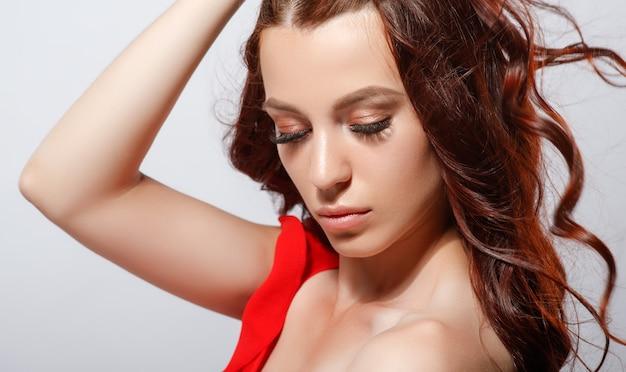 Studio glamour close-up portret van een mooie vrouw met luxe haar op een lichte achtergrond.