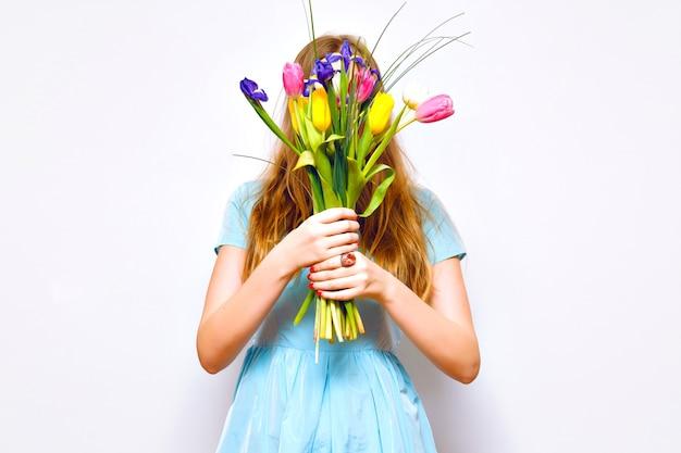 Studio grappig portret van blonde vrouw sluit haar gezicht door mooi boeket van kleurrijke tulpen, tedere pastelkleuren, vintage jurk, lange haren, modedetails. de lente komt eraan