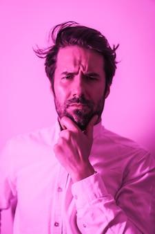 Studio lifestyle, portret van een serieuze blanke jongeman in een wit overhemd, verlicht met een roze neonlicht