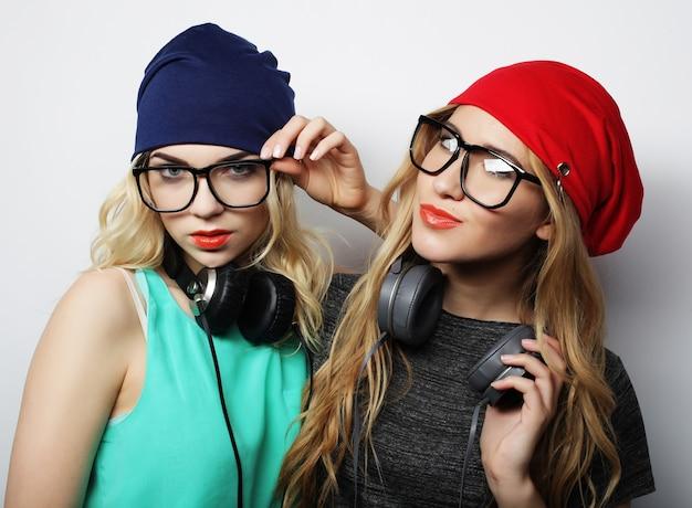 Studio lifestyle portret van twee beste vrienden hipster meisjes met stijlvolle heldere outfits, hoeden, denim shorts en brillen, gek worden en geweldige tijd samen hebben. jong en schoonheid.