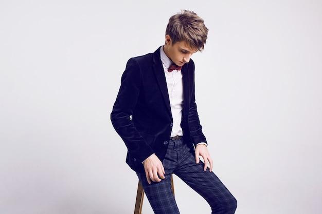 Studio mode portret van knappe mannen in stijlvol luxe pak en strikje, lichte achtergrond, zachte kleuren.