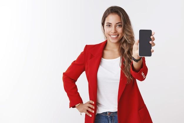 Studio-opname aangenaam glimlachend gelukkig blond kaukasisch meisje glimlachend witte tanden met smartphone-scherm, staande zelfverzekerde presentatietoepassing, suggererend gebruik app witte muur