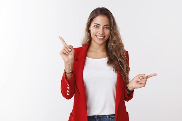 Studio opname aantrekkelijke vriendelijke lachende gelukkige blanke 25s vrouw met rode jas wijzend zijwaarts verschillende richtingen glimlachend presenterende keuzes glimlachen suggereren goederen, witte muur