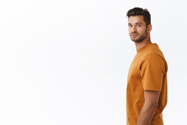 Studio-opname charismatische hipster man met baard in bruin t-shirt, staande in profiel linkerkant, hoofd naar de camera draaiend en glimlachen, iets interessants zien, aandacht vestigen op goede promotie