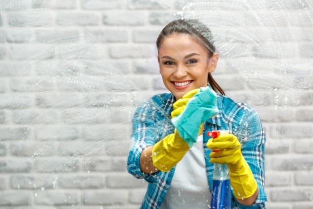 Studio opname door glas huishoudster. mooie vrouw schoonmaak venster. vrouw die handschoenen draagt, glimlacht en een fles met ontsmettingsmiddel vasthoudt