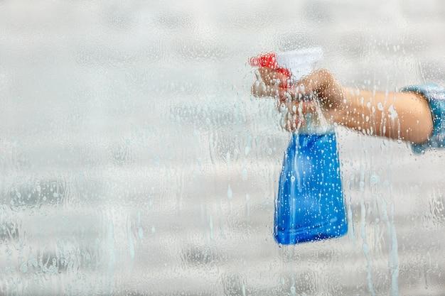 Studio opname door glas huishoudster. vrouw hand met fles spray. focus bij de hand