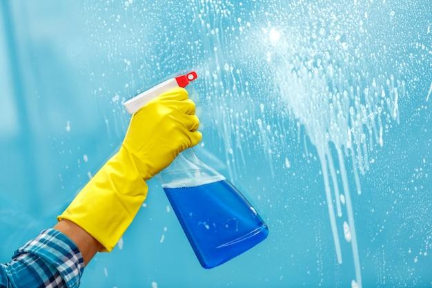 Studio opname door glas huishoudster. vrouw hand met handschoen fles spray te houden. focus bij de hand
