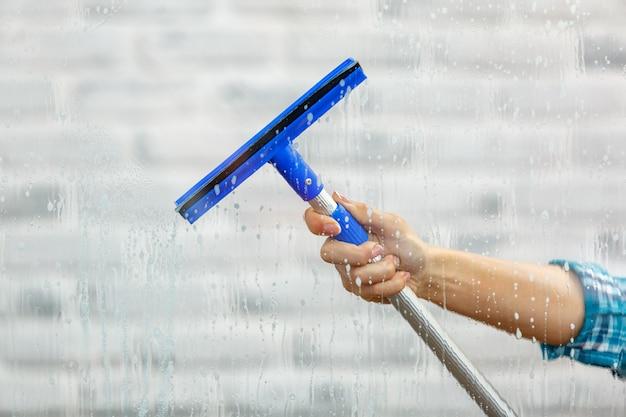 Studio opname door glas huishoudster. vrouw hand met wisser voor raam. focus bij de hand