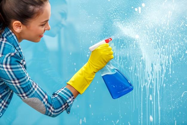 Studio opname door glas huishoudster. vrouw met handschoenen met fles spray. focus bij de hand
