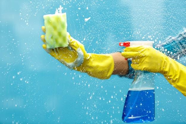 Studio opname door glas huishoudster. vrouwenhand met handschoen die een fles spray vasthoudt en een spons gebruikt om het raam schoon te maken. focus bij de hand