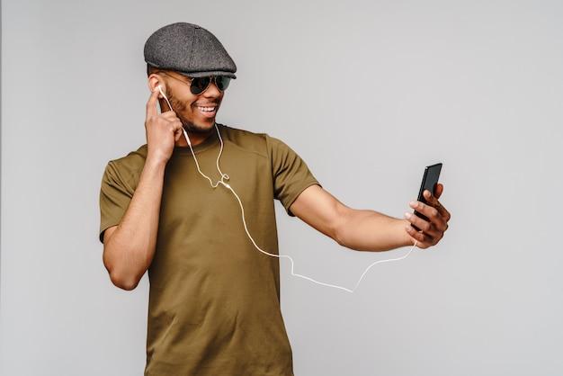 Studio-opname jonge afro-amerikaanse man luisteren naar muziek met een koptelefoon