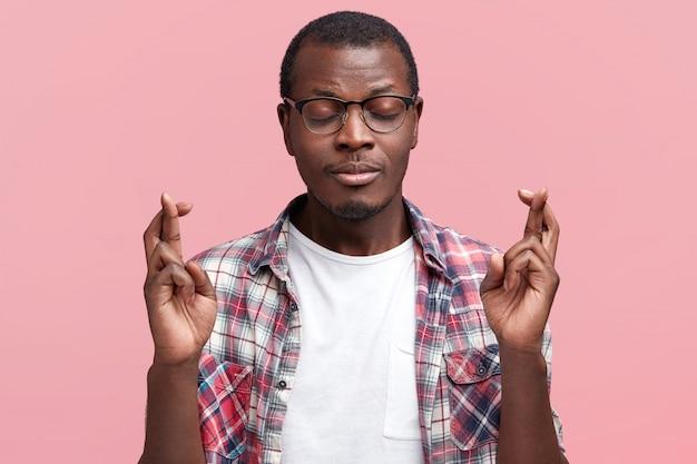 Studio-opname van de gewenste jonge afrikaanse amerikaanse man houdt vingers gekruist en ogen dicht, gekleed in een casual geruit overhemd, hoopt op het werk gepromoveerd te worden of een baan te krijgen